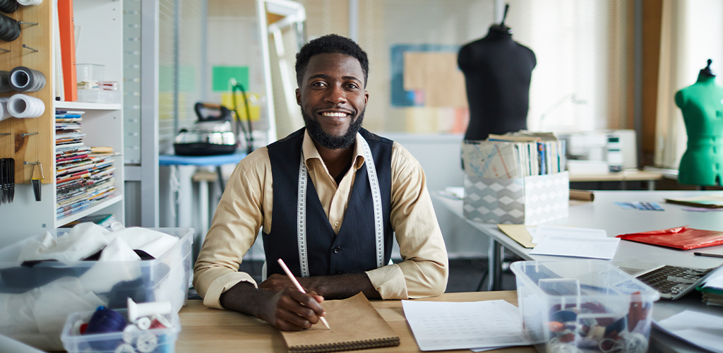 A self-employed man works in his office as a tailor.